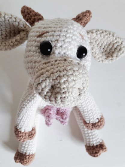 an overhead angle of a white, crochet cow toy, looking into the camera while sitting on a white table top