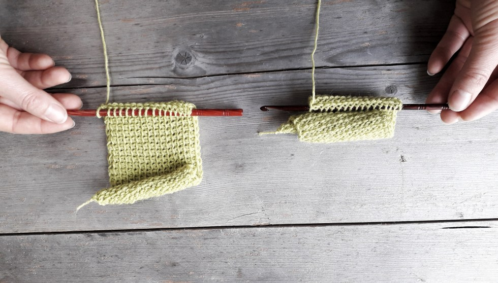two pieces of light green tunisian crochet on a faded wooden surface. The fabric on the right is tightly curled, the fabric on the left has a relaxed curl. Both pieces are still attached to crochet hooks