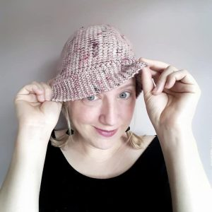 a woman is standing facing the camera, wearing a light pink tunisian crochet slouchy hat