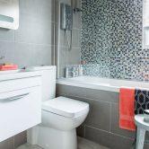 Parlak yeşil mozaiklere sahip küçük gri banyo