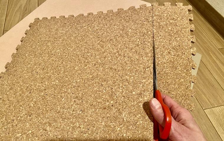 コルクマットの敷き方の画像8。コルクマットに付いたカッターの線に沿って、ハサミで切っています。