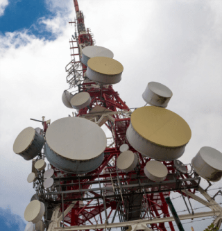 image presenting and crowdy telecom tower with a lot of large, expensive, microwaves backhaul antennas