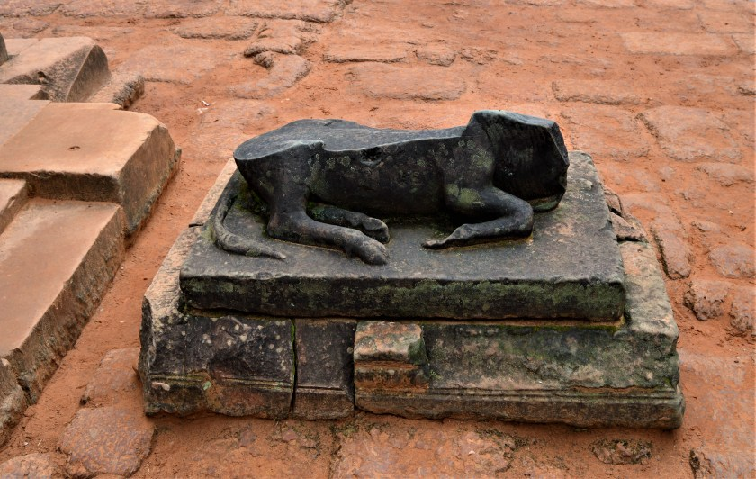Damaged statue of Nandi the bull located in front of innermost eastern gopura of the Banteay Srei temple
