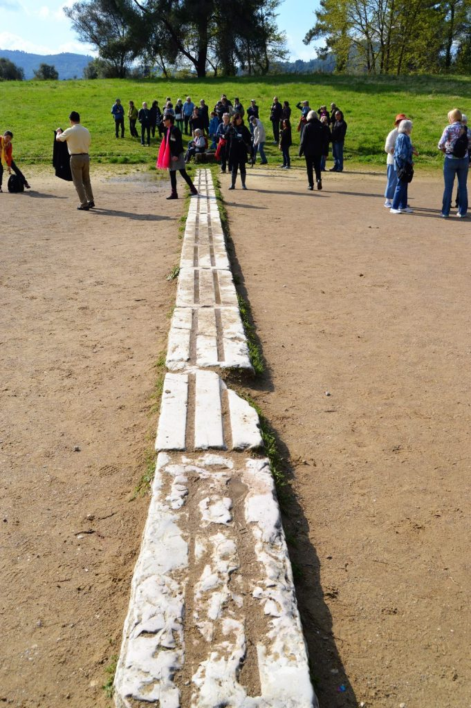 Starting line marker embedded on the race track at the ancient stadium at Olympia, Greece