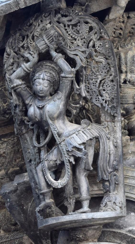 Tribhangi - A davane playing shilābālike with the tribhanga pose mounted on a pillar of the Chennakeshava Temple in Belur, Karnataka