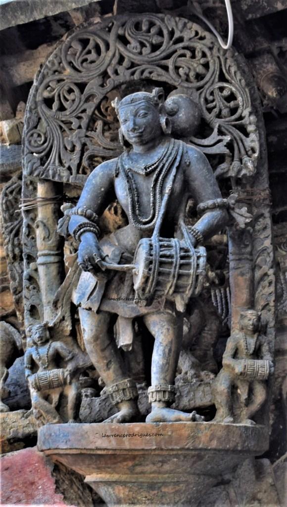 Davane playing male musician - A bracket figure mounterd on the exterior wall of the Belur Chennakeshava Temple in Karnataka, India