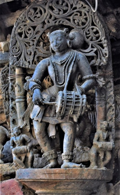 Belur Chennakeshava Temple -Sculpture of a dolu playing male musician mounted on a pillar