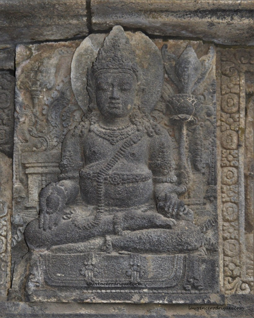Sculptural relief depicting Kubera holding a pomegranate with his right hand in the Shiva Temple in Prambanan located in Yogyakarta, Indonesia