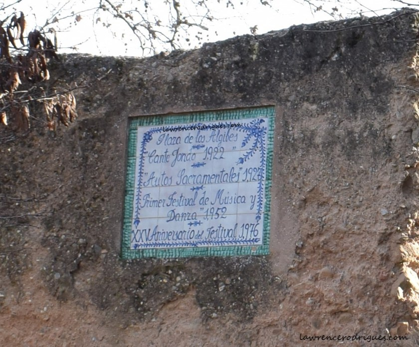Plaque listing the events held in the Plaza de los Aljibes embedded in the wall surrounding the Alcazaba in the Alhambra, Spain