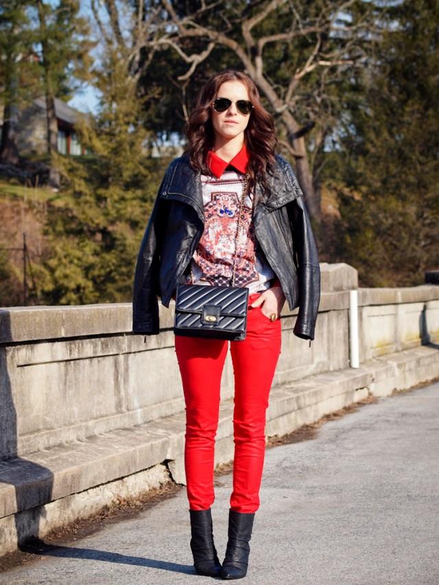 Красные джинсы с черной кожаной курткой и светлой кофточкой с принтом.