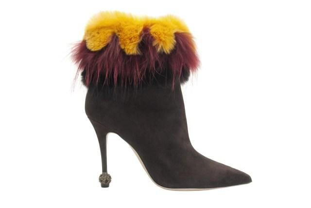 На фото: черные замшевые сапоги необычном на тонком каблуке с желто коричневым мехом от Manolo Blahnik.