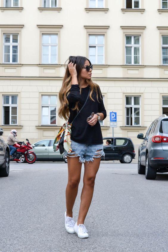 На фото: рваные джинсовые шорты с черным свитером и белыми кроссовками.