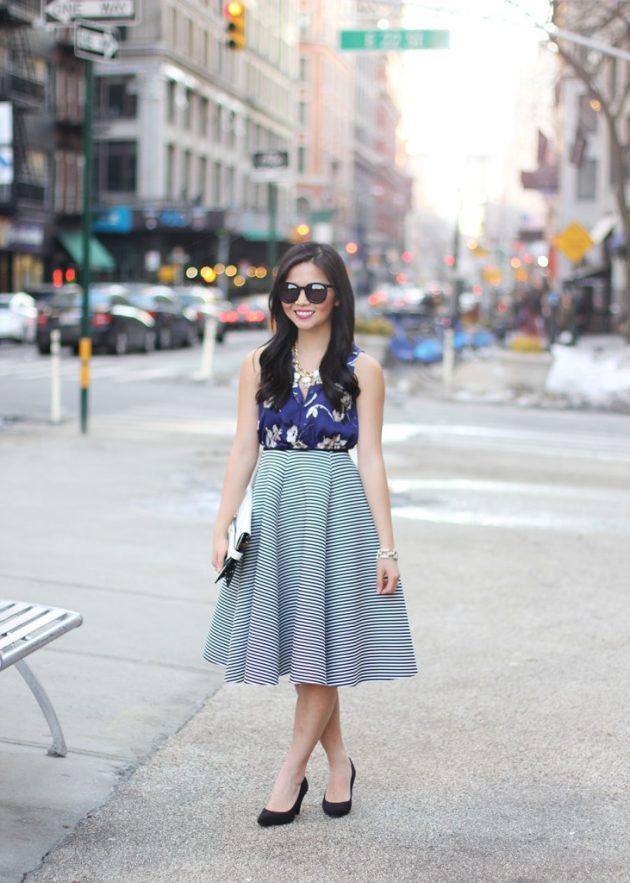 На фото: пышная юбка миди с черной блузкой с цветочным принтом.