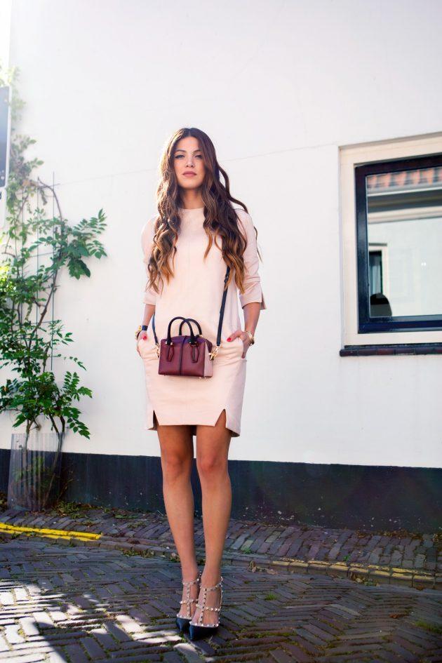 На фото: короткое розовое платье прямого покроя с разрезами вдоль длинных рукавов и длины платья.