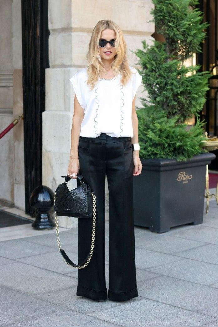 На фото: черные брюки прямого силуэта с белой блузкой с украшенной декором верхней частью.