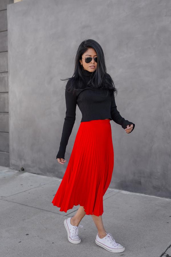На фото: белые кеды Converse в сочетании с красной юбкой и черной кофтой.