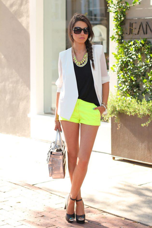 На фото: неоновые зеленые шорты с черным топом и белым пиджаком.