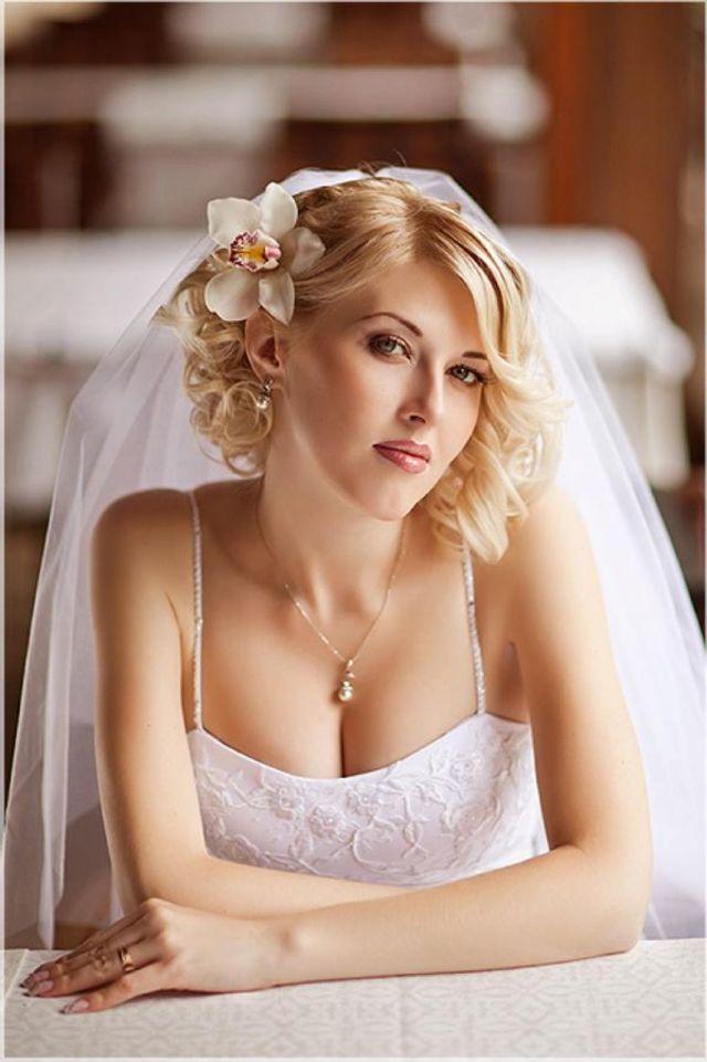 На фото: свадебная короткая причёска  с фатой и с цветком сбоку в волосах.