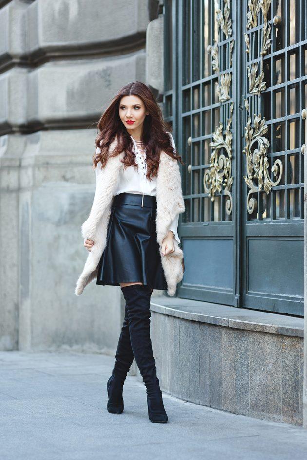 На фото: короткая раслешенная черная кожаная юбка с завышенной талией яркое сочетание со светлым верхом.