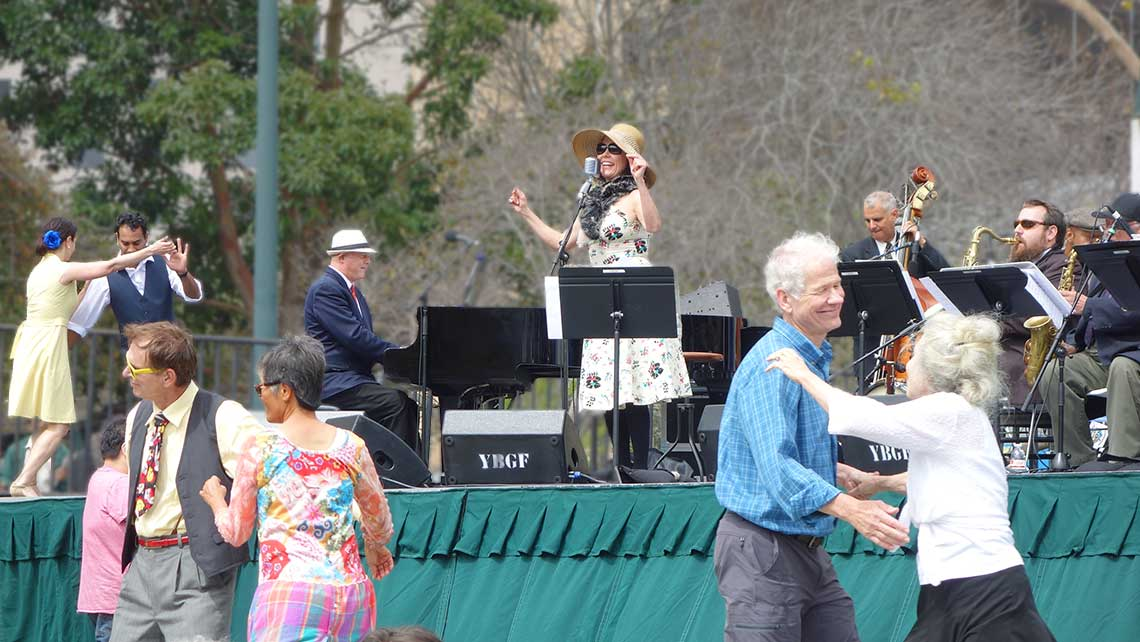 Photo of Lavay Smith and Chris Siebert on stage with swing dancers around