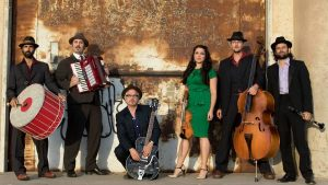Photo of klezmer band Kugelplex, with band members standing ing a row holding their instruments