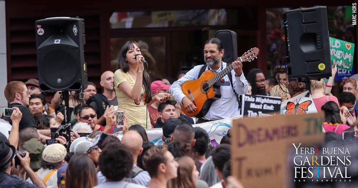 Photo of singer Diana Gameros holding a microphone and Francisco Herrera playing the acoustic guitar while surrounded by a street crowd. Photo by Marc Hors.