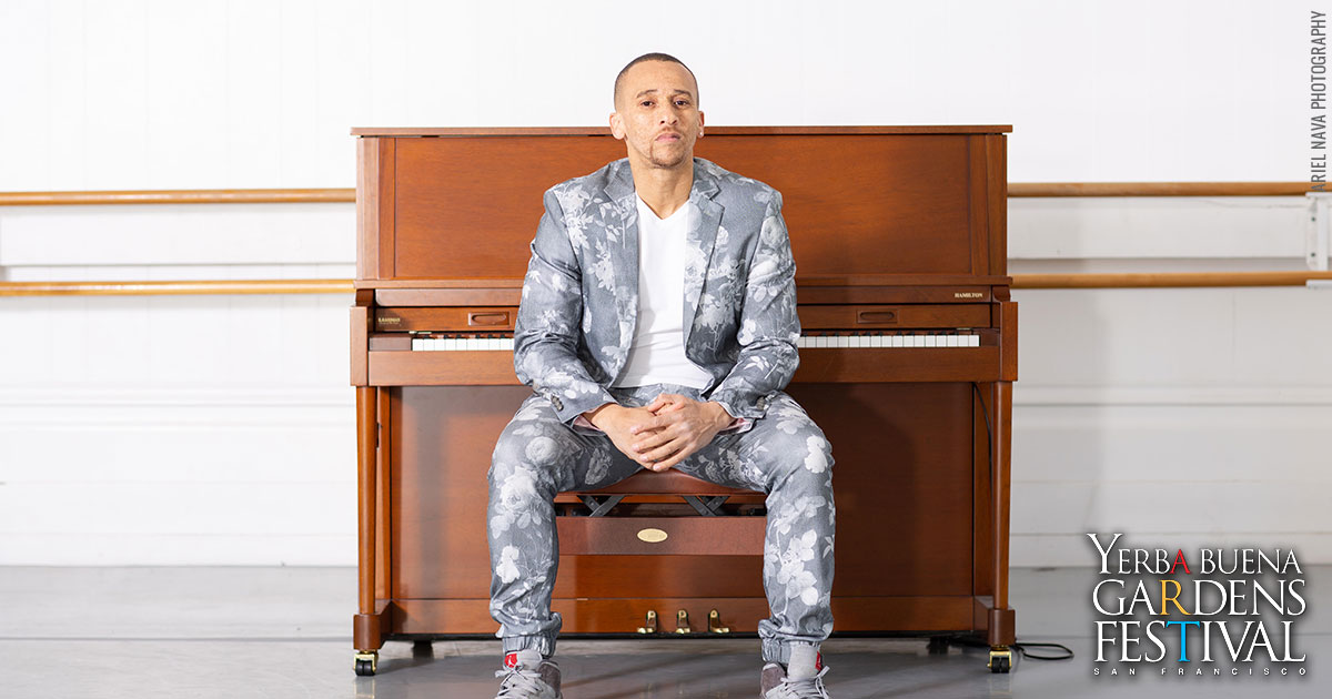Photo of musician Kev Choice sitting in front of an upright piano.