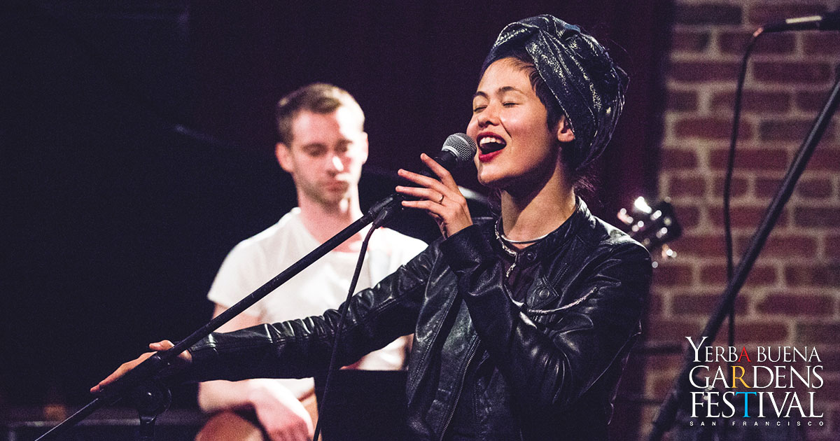 Singer Camille Mai in black jacket, in a dark room on a stage, holding and singing into a microphone. A guitar player and a brick wall behind her.