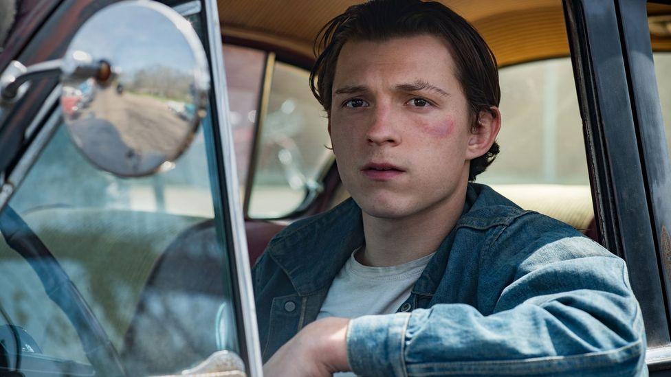 The Devil All the Time'ın başlıca odak noktalarından biri, mutsuz bir soydan gelen ve intikam eğilimi olan genç bir adam olan Arvin (Tom Holland) (Kredi: Netflix)