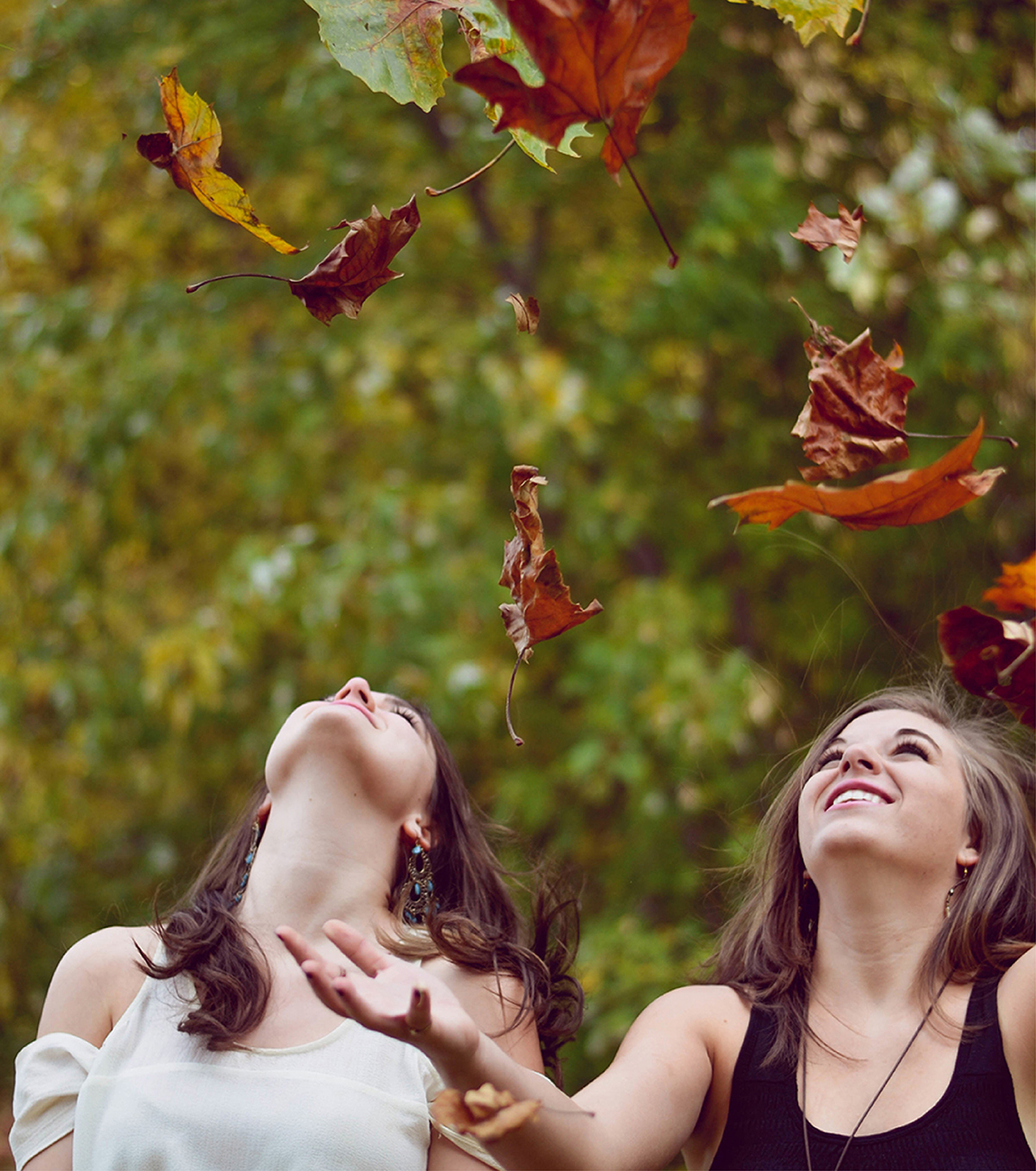 Girls throwing leaves into the air