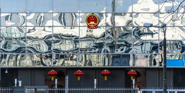 Peiliseinäinen rakennuksen julkisivu, jonka yläosassa on Kiinan vaakuna ja alaosassa punaisia lyhtyjä.