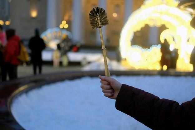Käsi, joka pitelee kullanväristä vessaharjaa; taustalla lunta sekä talvivaatteisiin pukeutuneita ihmisiä
