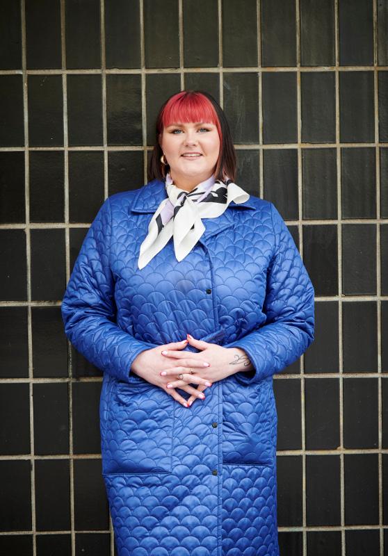 Anni Marttinen päällään sininen ulkotakki, selkä tummaa tiiliseinää vasten.