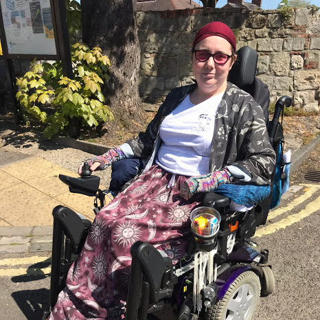 Helen Jones in her electric wheelchair looking at the camera and smiling