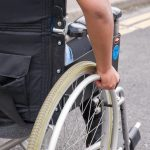The side rear view of a manual wheelchair being self propelled