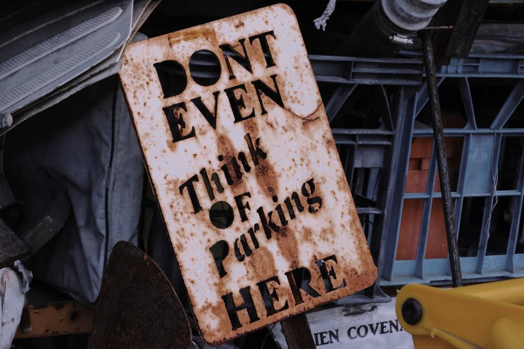 A rusty sign reads 'don't even think of parking here'