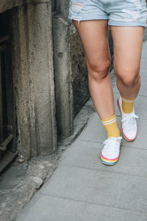yellowgirl_Sommeroutfit in Jeans-Shorts Band-Shirt, Regenbogen Sneakers und gelben Sportsocken (6 von 11)