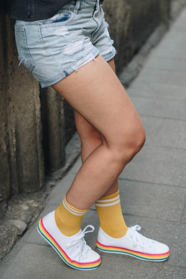 yellowgirl_Sommeroutfit in Jeans-Shorts Band-Shirt, Regenbogen Sneakers und gelben Sportsocken (7 von 11)