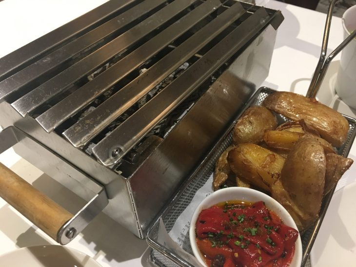 Patatas y pimientos rojos asados y una parrilla