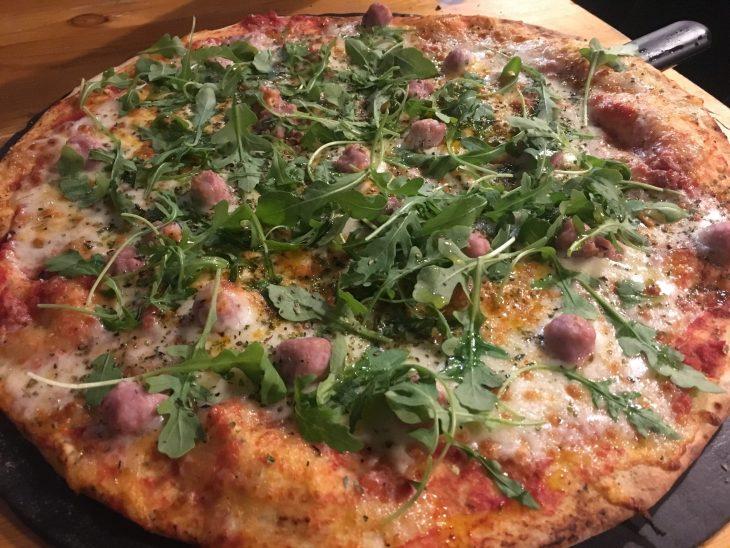 Pizza de mascarpone, tomate seco, bocconcini, salchicha y rúcula