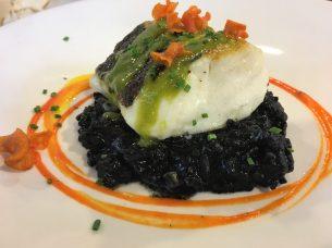 Lomo de merluza con arroz negro y una vinagreta de anchoas y aceitunas negras