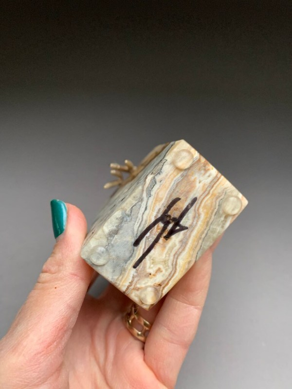 Yenny Cocq signature on natural stone base