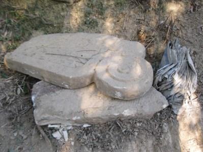 Những phiến đá có họa tiết hoa văn nằm lăn lóc.