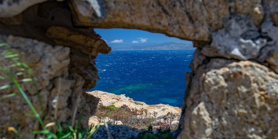 The blue sea of Sardinia from above between the cracks of a stone arch