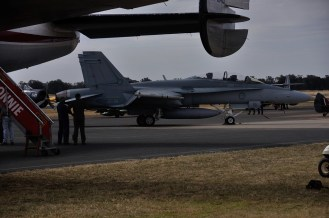The F18 sits waiting to go while the crew of the Connie look on