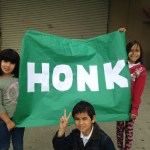 "A photo of children in Salinas, CA holding a green banner reading ""Honk"". Part of the Honk for Peace rally, May 2014."