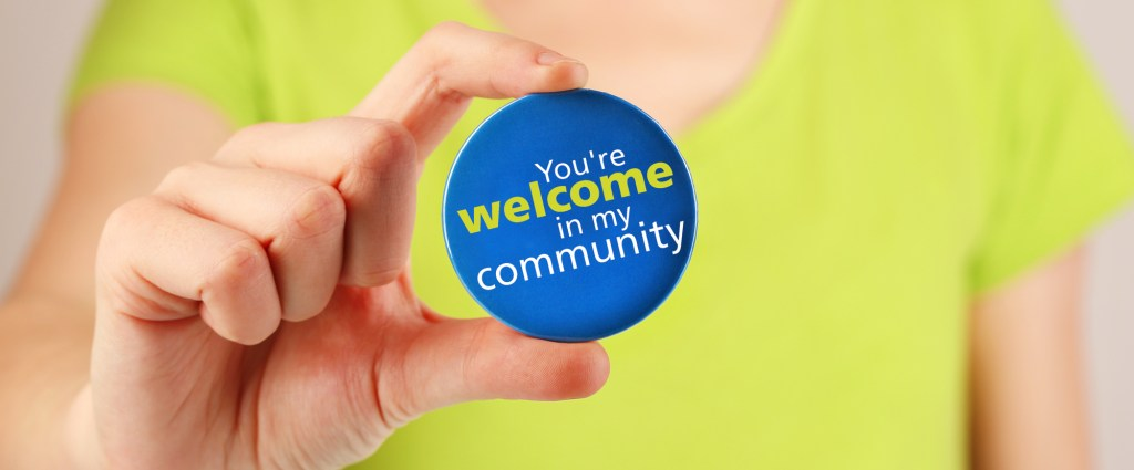 Person holding a button that says you are welcome in my community