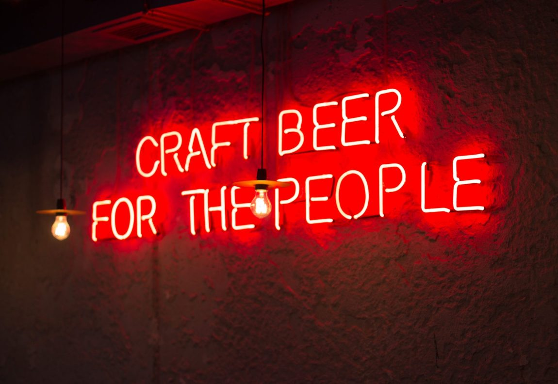 "Red neon sign in bar reading ""Craft Beer For The People"""