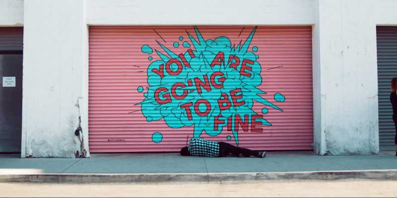 "Image of homeless person sleeping under street art that reads ""you are going to be fine"""