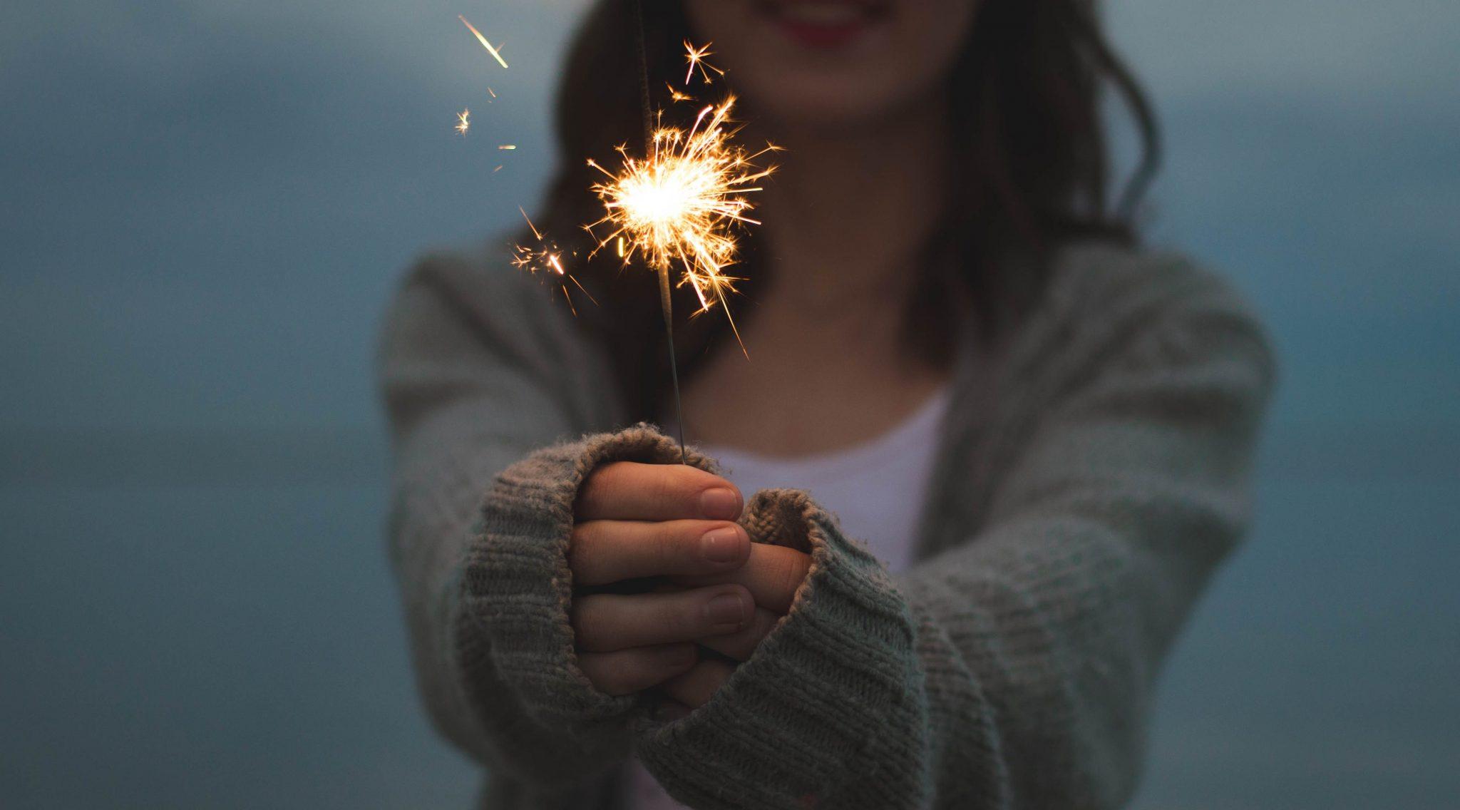 woman holding sparkler on the beach
